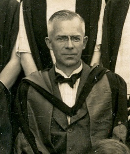 Black and white photograph of P W Bryan wearing academic dress, from the class photograph of 1925 (ULA/FG5/1/3)