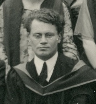 Black and white photograph of Philip Leon wearing academic dress and spectacles.
