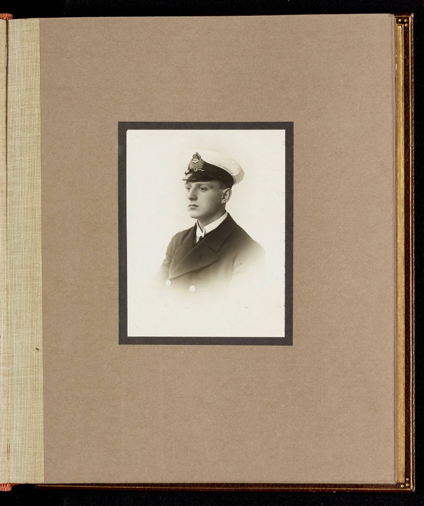 Mounted black and white photograph of Oliver Bernard Ellis from University of Leicester memorial portraits book. Ellis is wearing naval uniform.