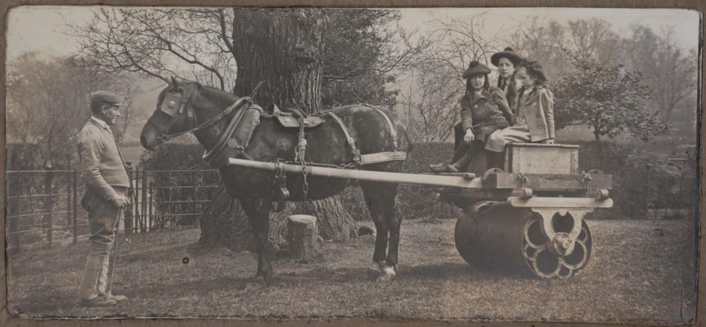 Black and white photograph of Bruce children having fun on the garden roller drawn by Spider and led by John Bird.