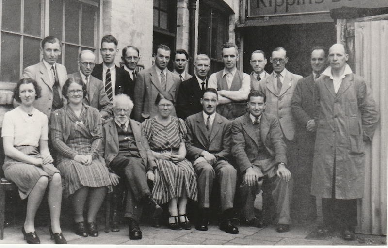 Black and white group photograph with Mollie Rippin, (front row, centre), outside Rippin's bookshop in Leicester.